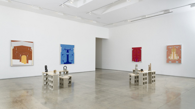 """Installation photo of four paintings along with a series of small sculptures mounted on """"plinths"""" made of cinderblocks."""