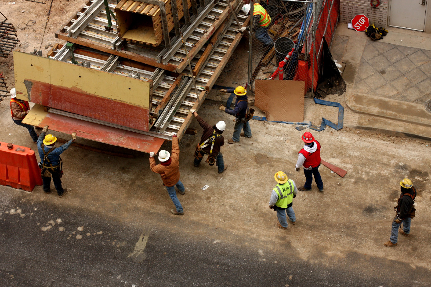 Photo of workers in hard hats and vests unloading construction materials from the back of a truck