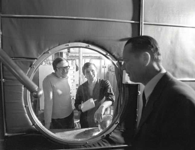 Black and white photo of two people looking through a porthole at an observer