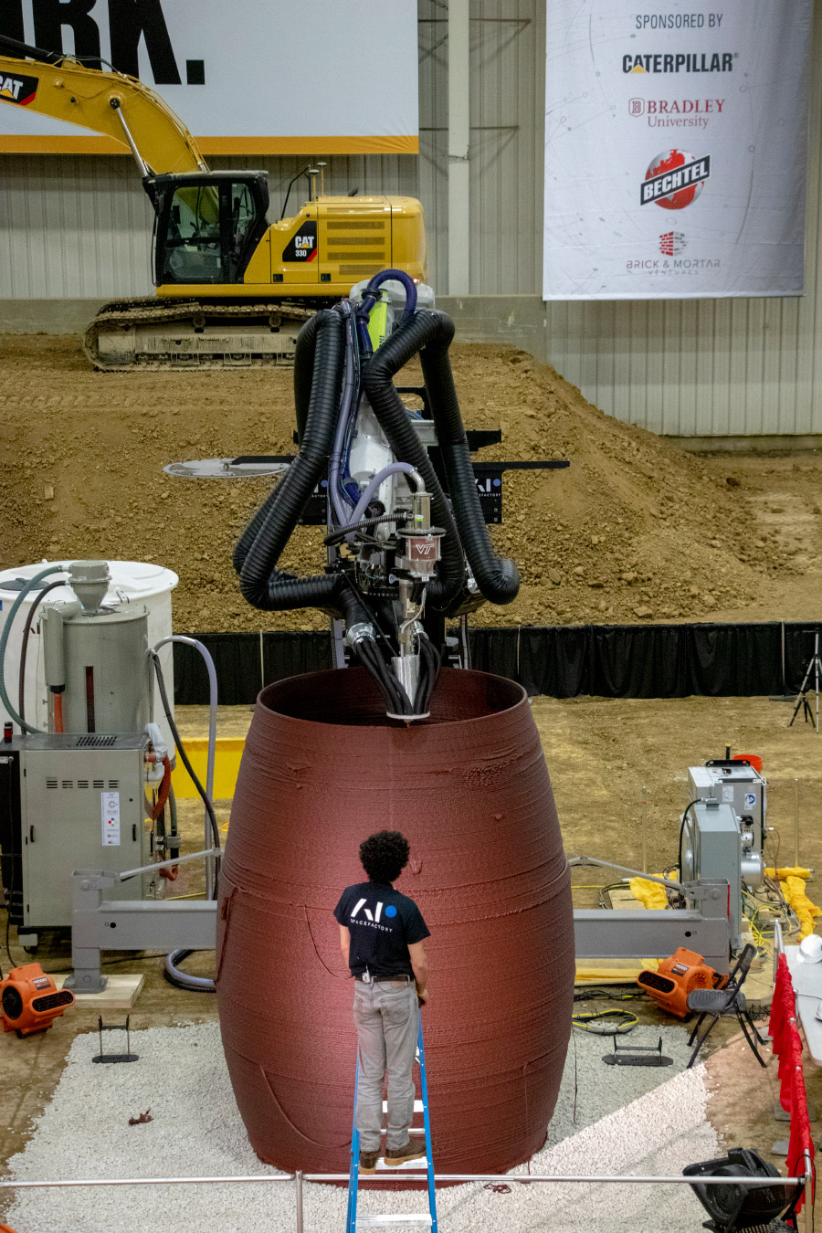Photo of a person standing in front of a cylinder that's being 3D printed, a model for space habitation