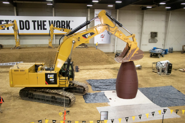 A backhoe pressing its arm down on a cylindrical concrete structure