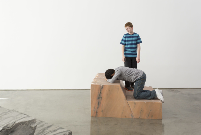 Photo of art installation with one young boy kneeling on a marble pedestal with another boy overlooking him