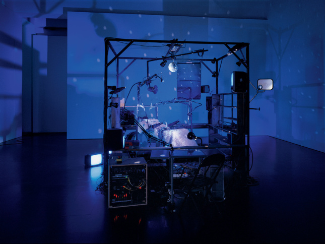 Photo of a gallery lit with blue light and an installation of a bed with various devices around it