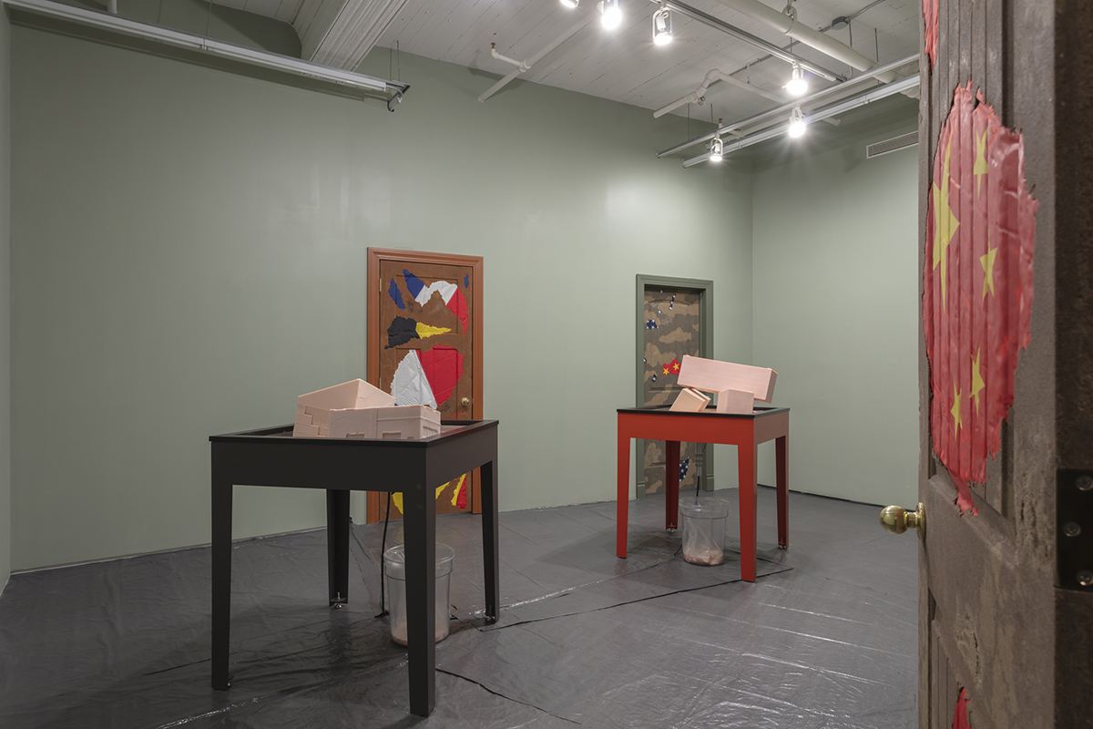 A door with a partial Chinese flag opens to a room with two tables, each with pink blocks partially melted on top. At back are additional doors with flag fragments.