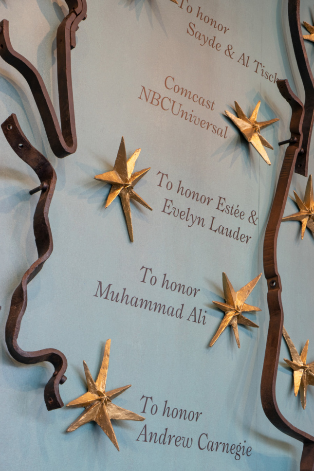 A copper wall with gold stars on it and strips of iron