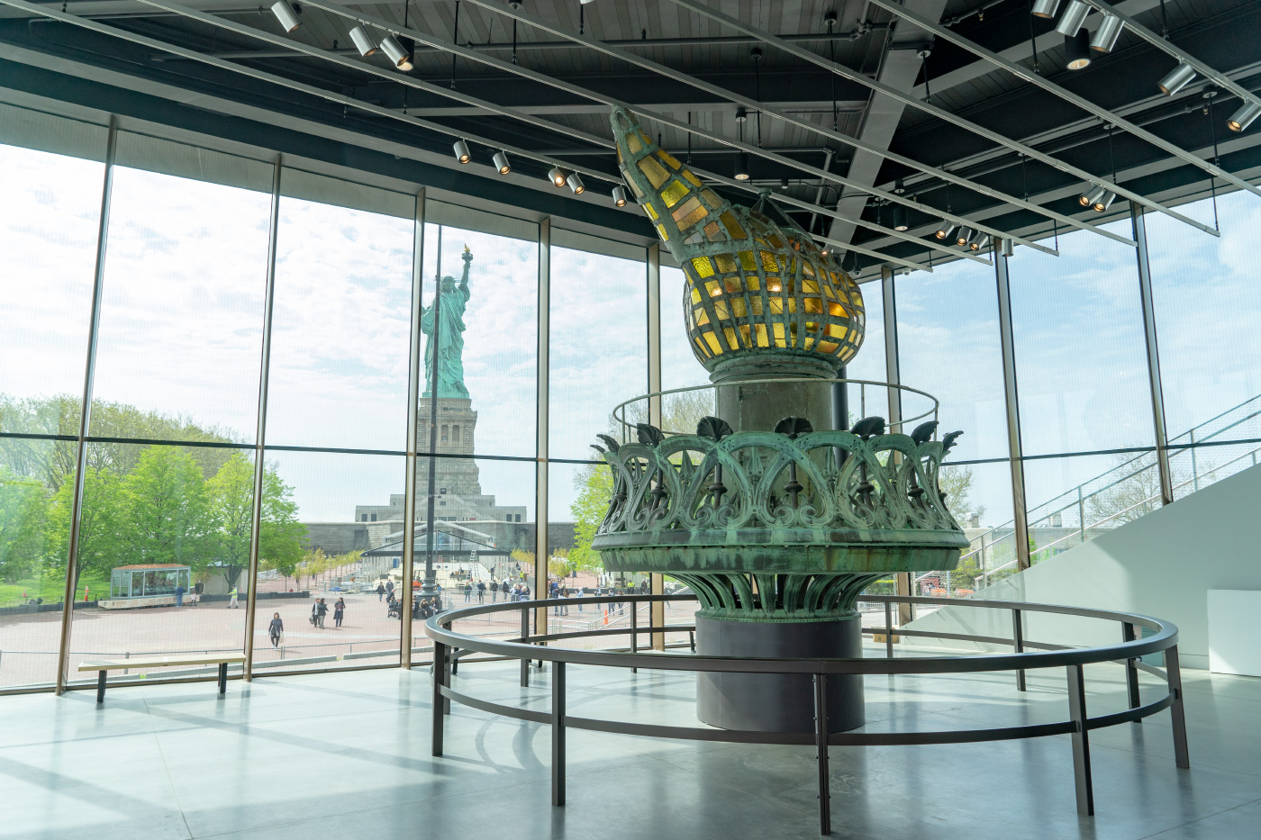 Photo of a multistory copper torch foregrounded against the Statue of Liberty