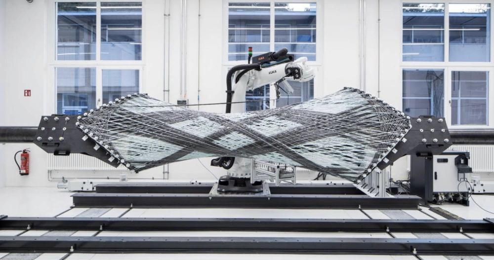 Photo of carbon fibers being woven by a robotic arm across two braces