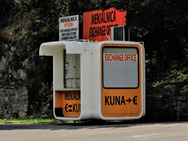 Photo of a rounded white kiosk advertising currency exchange