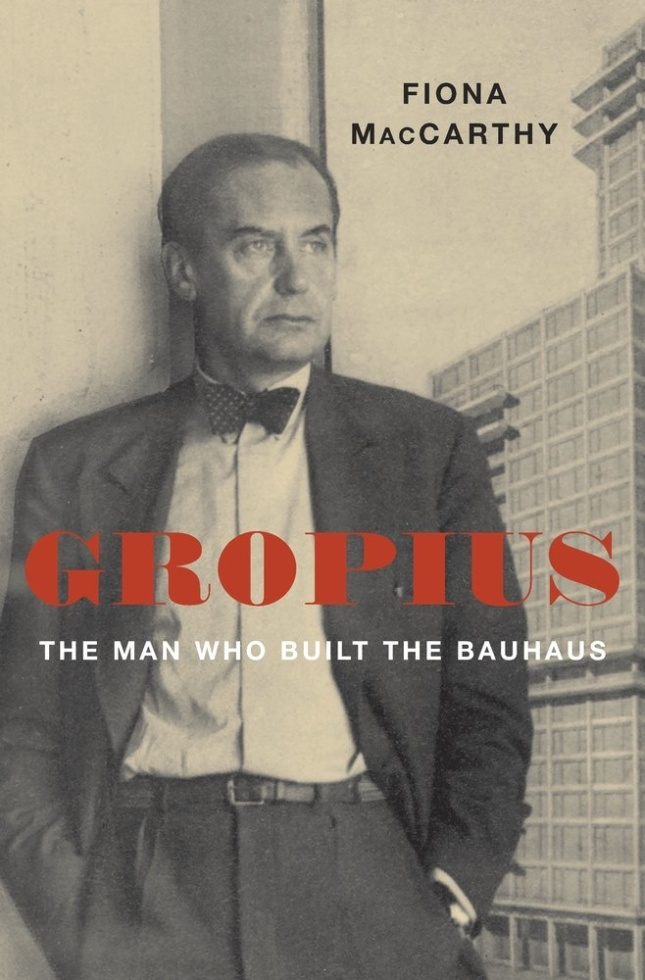 """A man leaning against a wall, with the text """"Gropius"""" over his chest"""