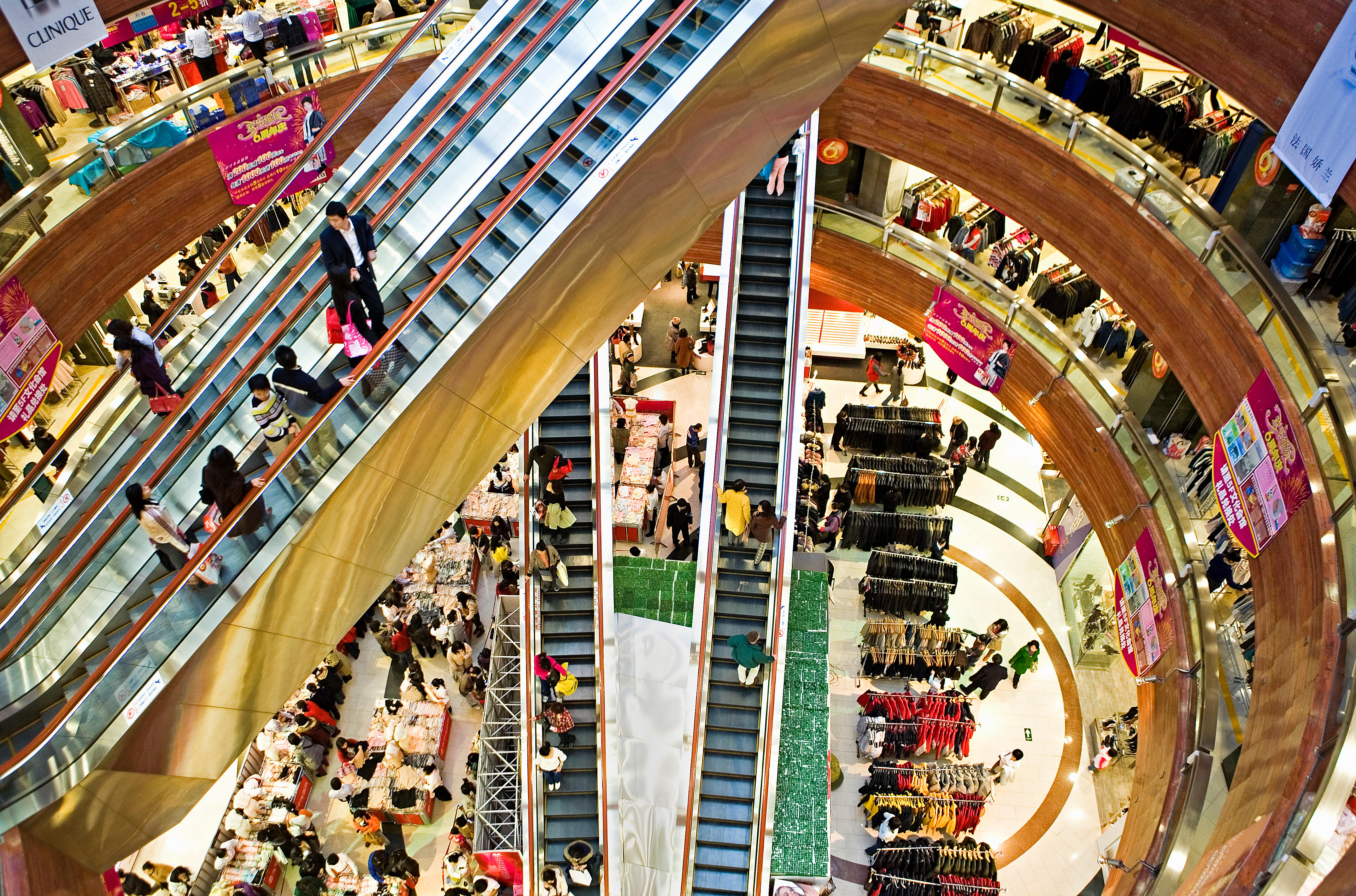 A top-down photo of intersecting gold-colored escalators in a shopping mall