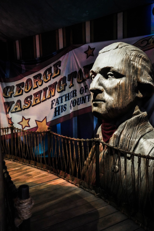 "A large wooden bust of George Washington sits next to a banner that reads ""George Washington, Father of his country"""