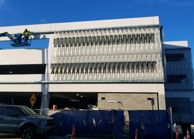 Exterior construction photo showing stainless steel mesh getting put on a facade