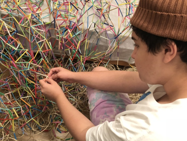 Photo of a teenager making a net out of colored plastic straws