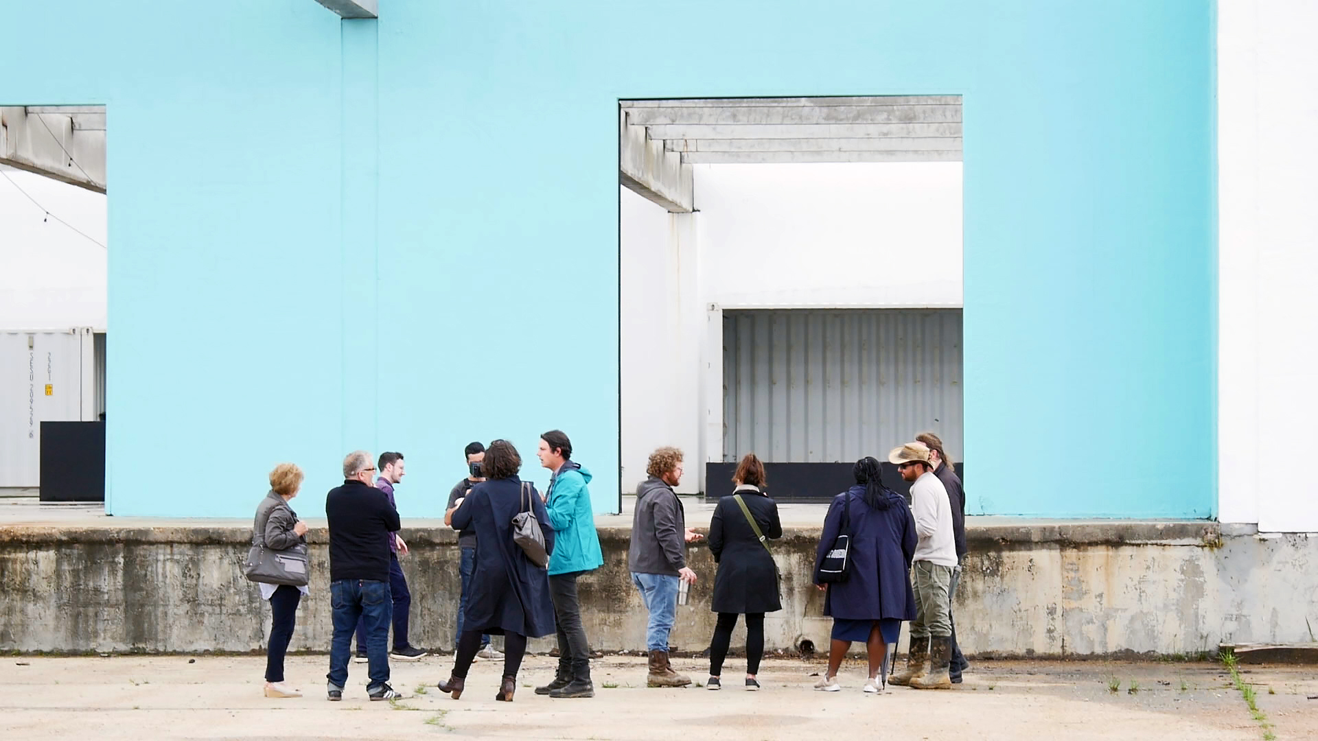 Photo of people standing in front of a light blue building wall