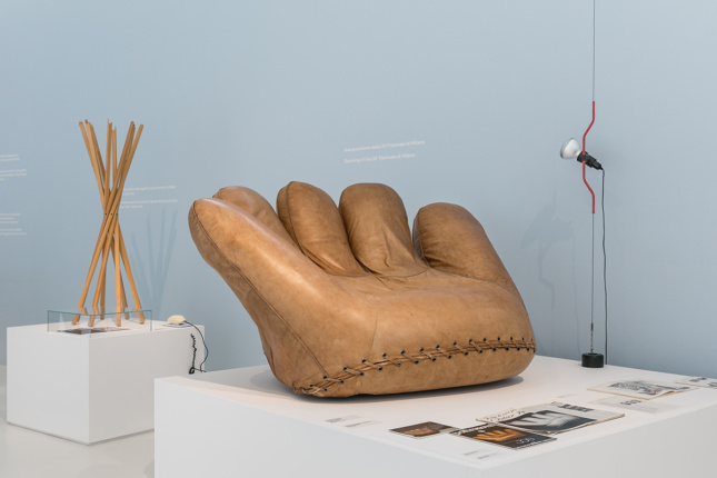 Photo of a sofa shaped like a catcher's mitt in a gallery