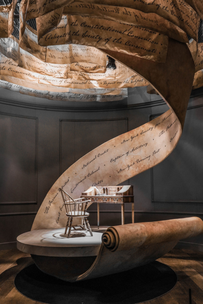 An antique writing desk with a large swirl of parchment that twirls overhead