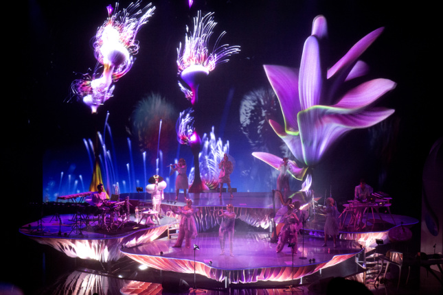 Musicians perform on purple platforms while imagery of fireworks and flowers are project large behind them.