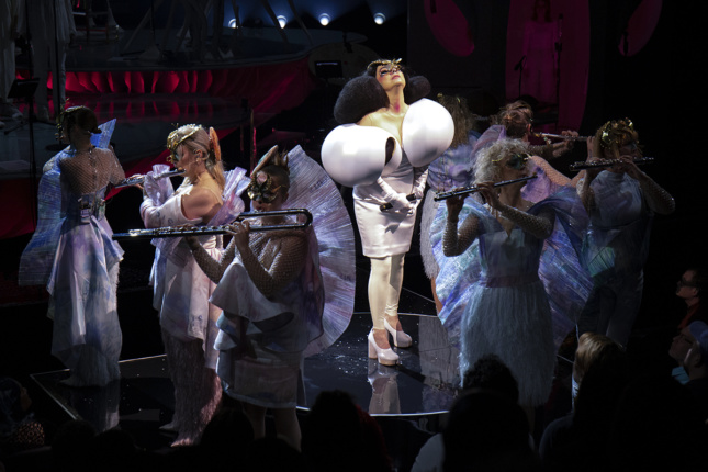 Björk stands center in a white dress with oversized shoulders while flautists, in white dresses with wing-like backs, play around her. They all wear masks.
