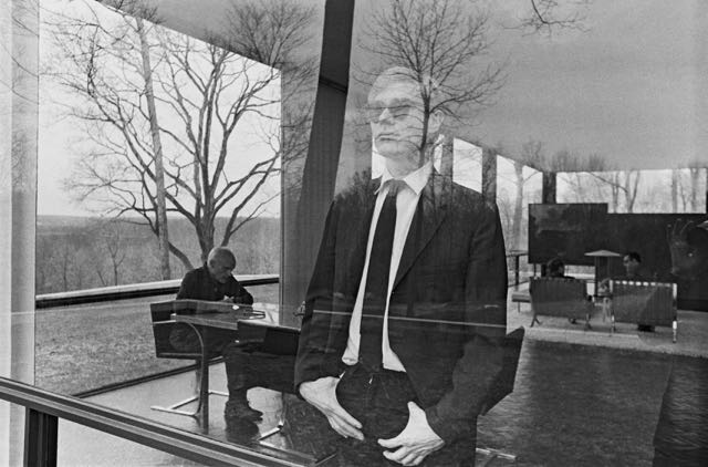 Photo of Andy Warhol looking out the window of The Glass House