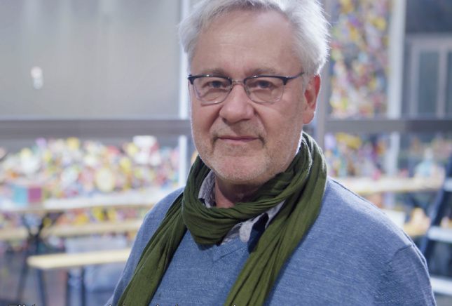 Headshot of an older man in a blue shirt with a scarf