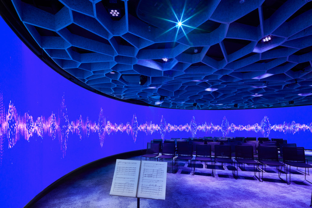 Photo of the Octave 9 interior, a round room with digital projections on the walls, mesh on the ceiling, and seats in the middle