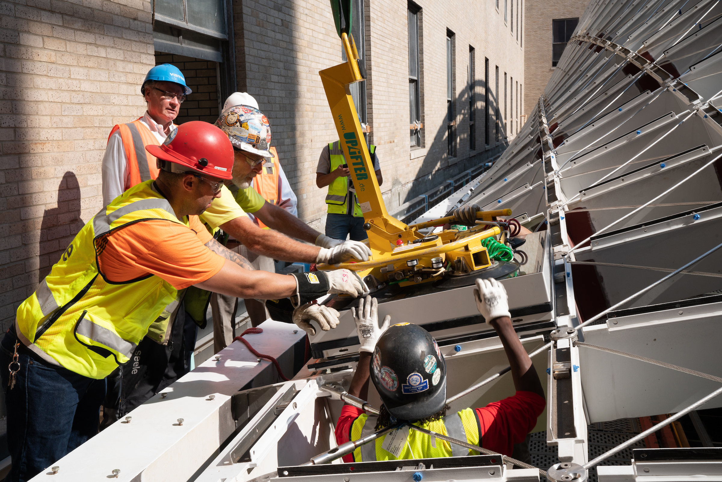 Construction workers at work on a metal frame.