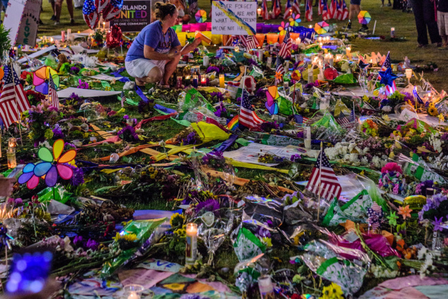 Photo of flags, letters, candles, and bears on a lawn