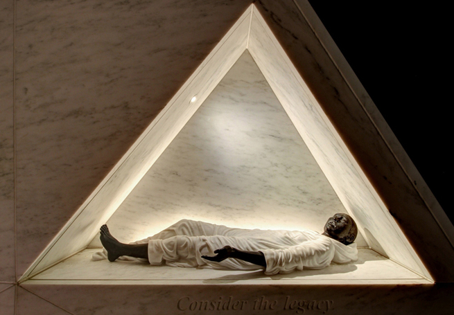Photo of a sculpture of a black man reclined in a triangular cut-out structure.