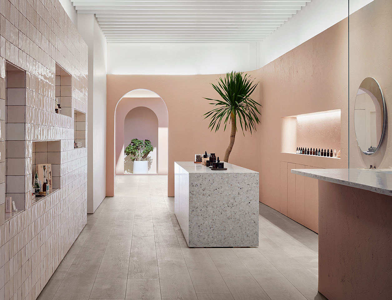 Photo of store interior with tile, terrazzo, and wood surfaces in warm, light tones