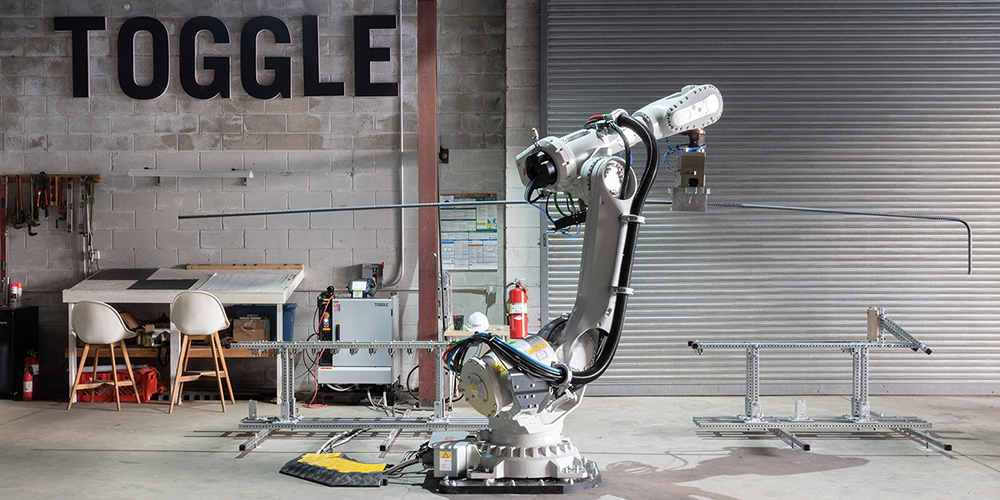 Photo of a robot arm in front of a sign reading