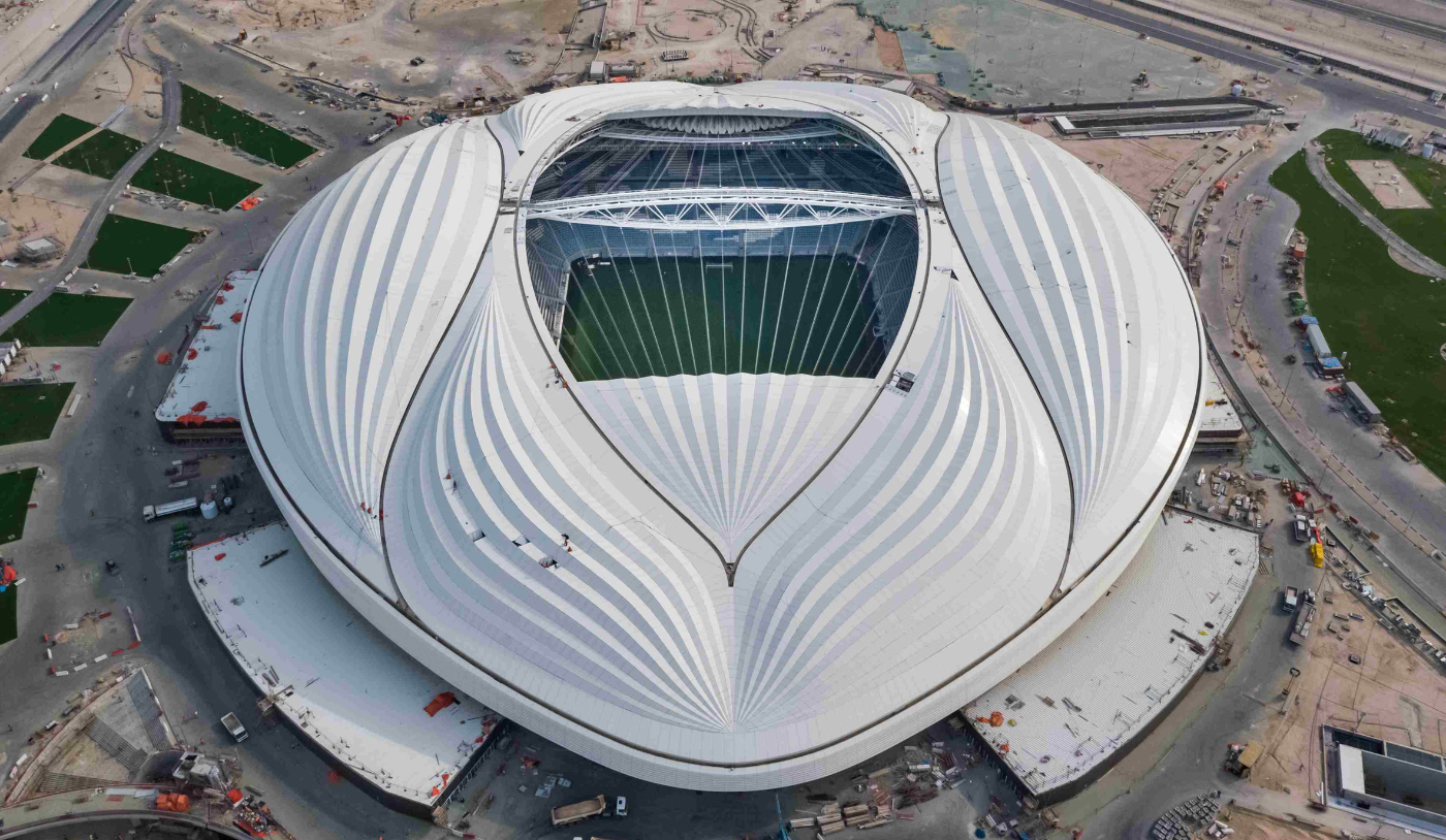 Aerial photo of a white, rounded stadium with curves