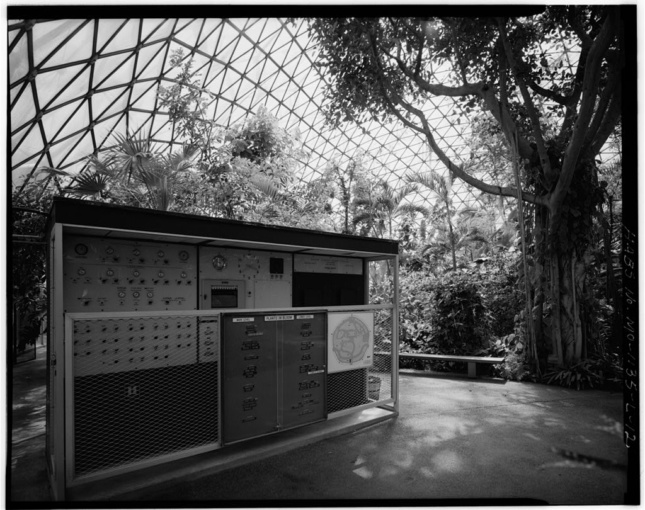 Black and white photo of the interior of a geodesic dome with a hut and many plants inside