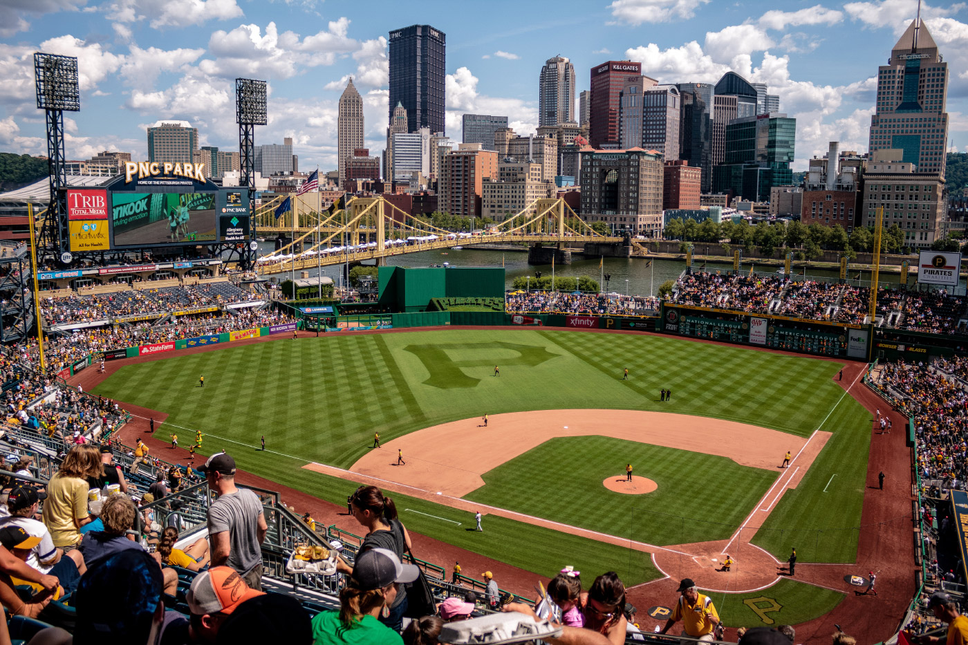 Photo of a ballpark with a skyline and bridge as a backdrop