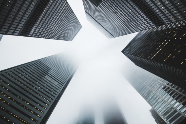 Photo looking up at tall buildings in the fog