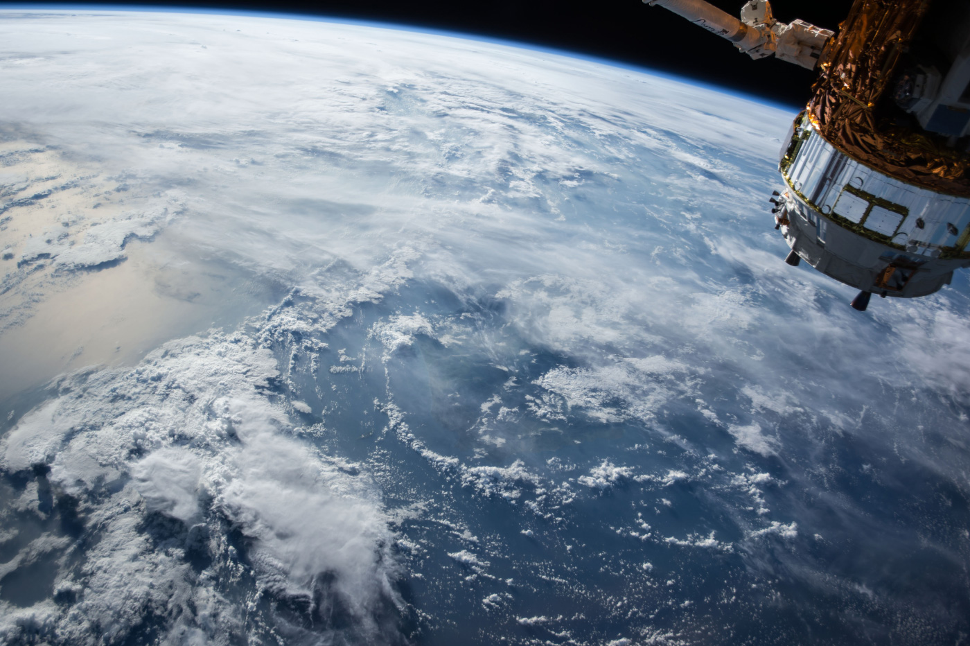 The Earth, as seen from space, with clouds moving across the surface