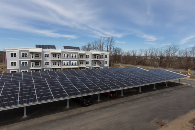 Photo of parking lot covered with solar panels with an apartment complex in the background