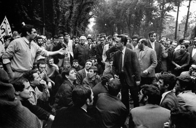 Students protesting as two men debate each other