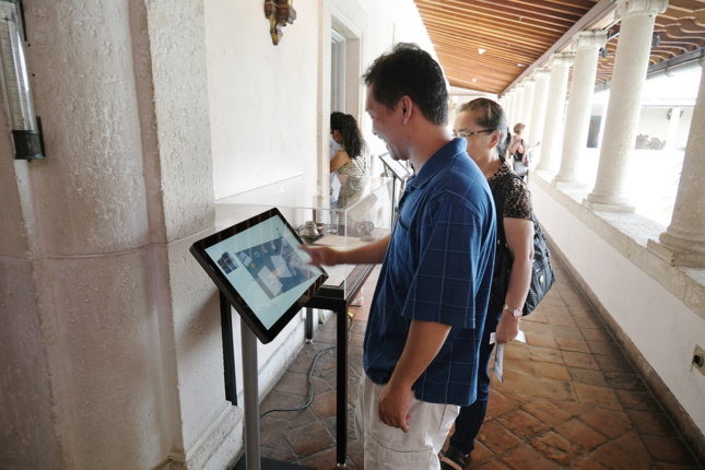 A museum visitor uses a large touch screen adjacent to a plexiglass display.