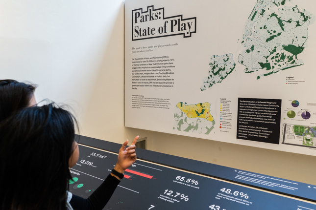 """Woman pointing at a board on a wall opposite that says """"Parks: State of Play"""""""