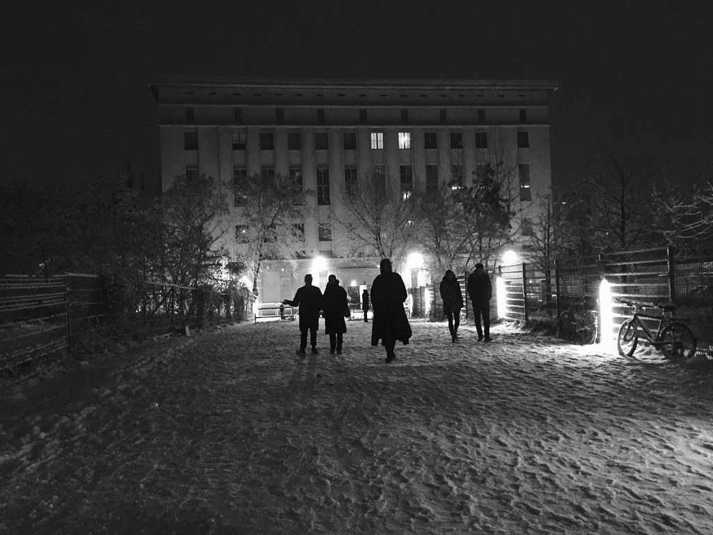 Black and white photo of people walking through the snow to Berghain in an old East Berlin power plant