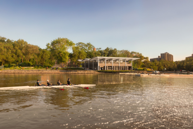 A timber boathouse with wooden awnings as seen from the river beside it