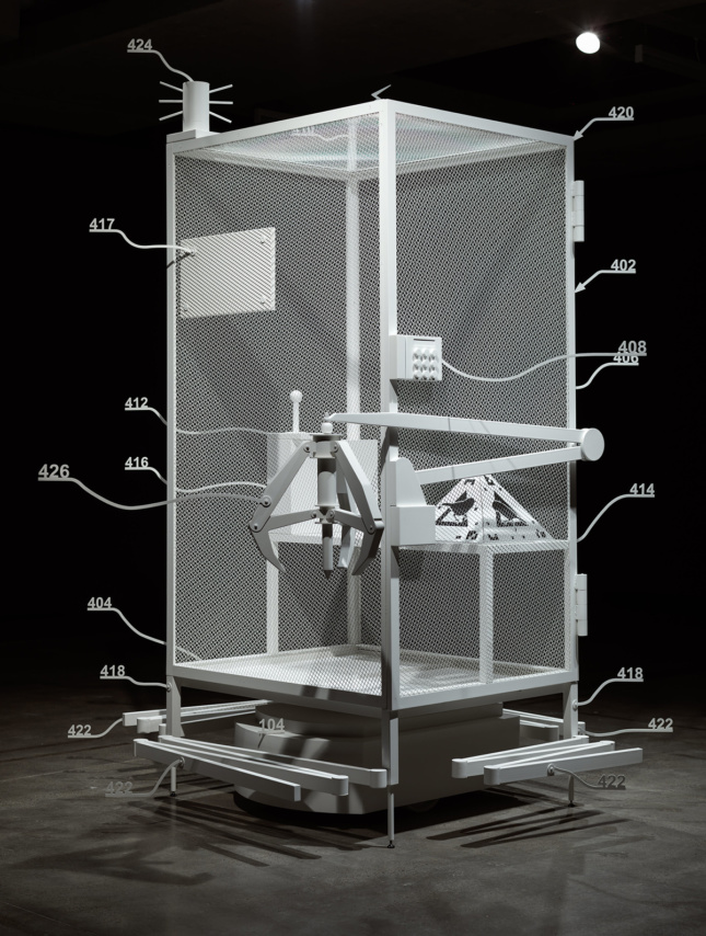 Photo of a white cage with numbers branching out in metal. A large claw is attached. Inside on a pyramid are black images of a bird.