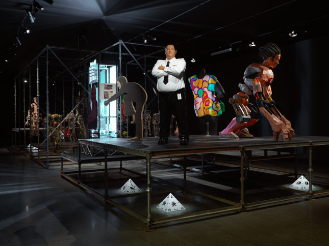 Photo of figurative sculptures of a man in a suit, a giant automaton, and others are on a large platform.