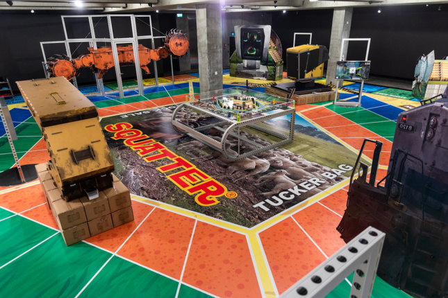 Photo of a large board game with a central image over some sheep and text reading SQUATTER has a variety of life-size realistic sculptures of mining machines on it.