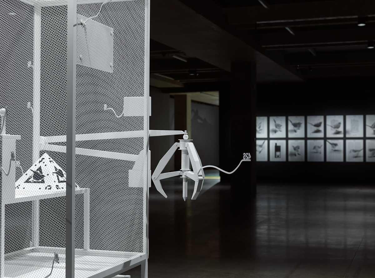 Photo of an edge of a white-ish metal cage with a claw with images of patents superimposed with birds mounted at the wall towards the back. The room is dark.