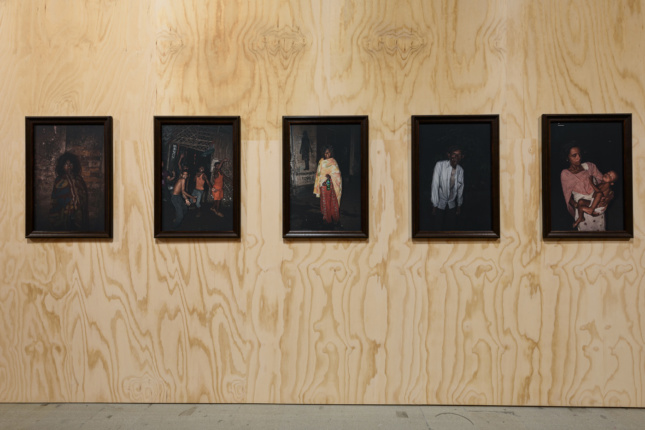 A plywood wall with five portraits on it, each depicting a disheveled homeless individual on a black background