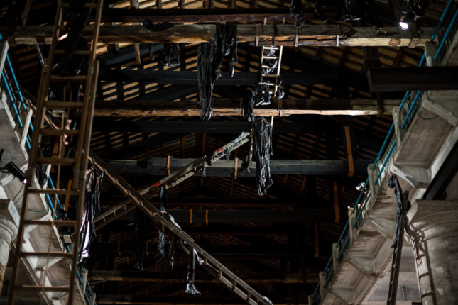 Figures from black latex suspended in wooden rafters