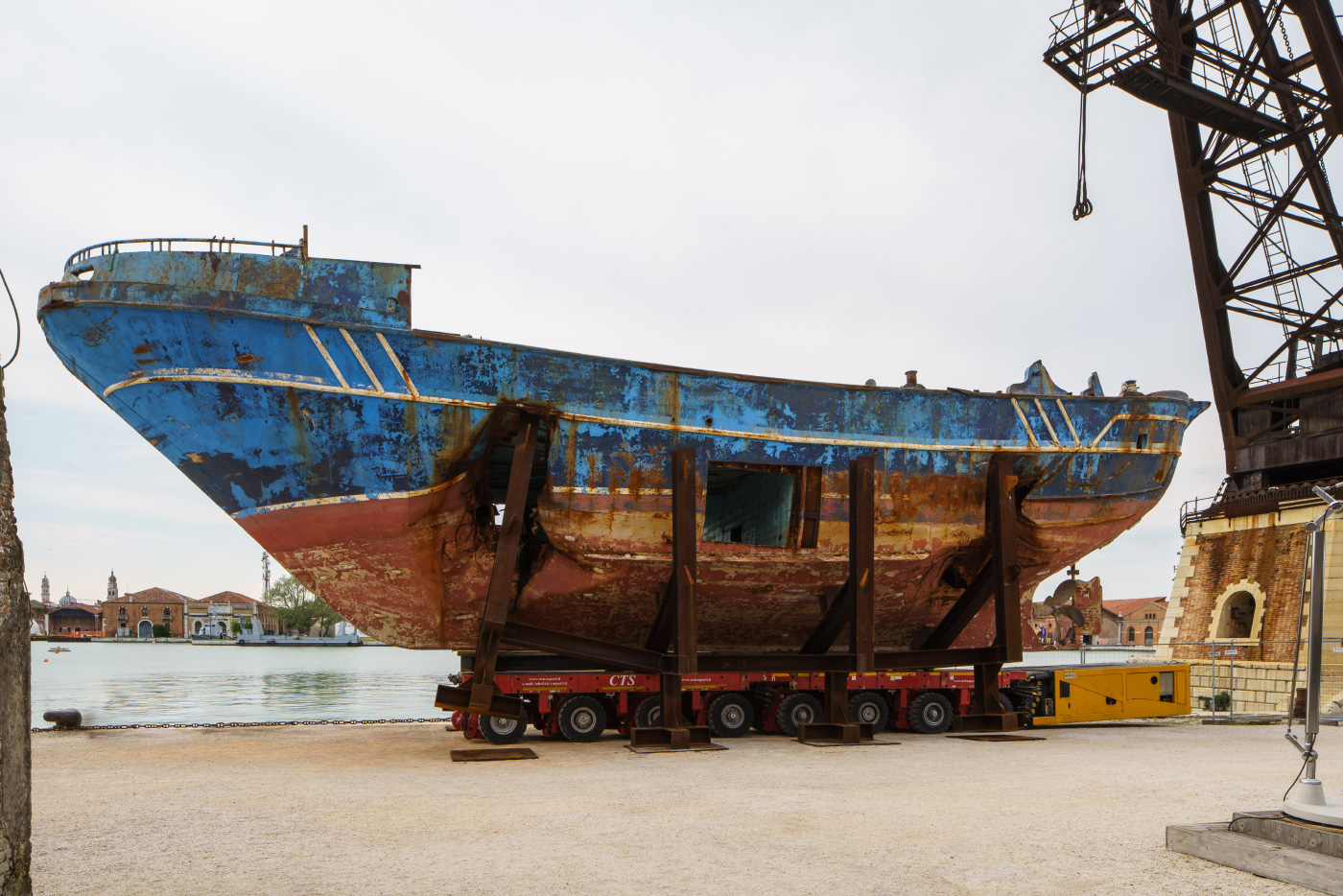 A rusted boat with a large gaping hole in the side of it, installed on concrete