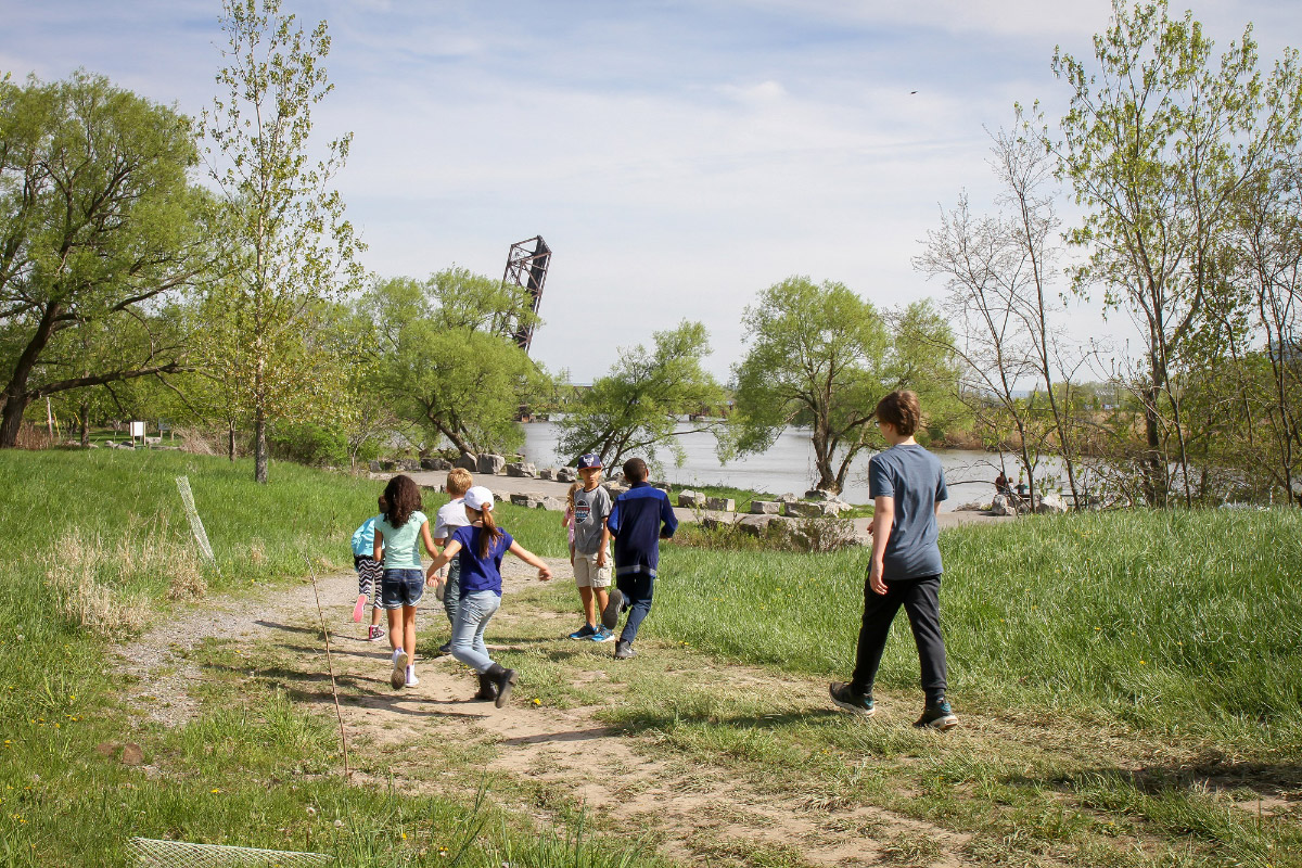 Photo of children running on grassy trail along river in the current DL&W Corridor