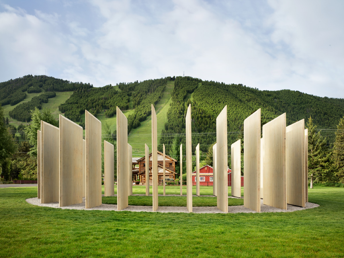 Photo of ring of raw timber panels arranged so that the mountain beyond is visible